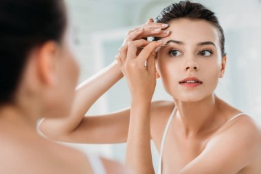 Beautiful girl correcting eyebrows with tweezers and looking at mirror in bathroom stock vector