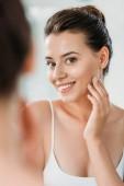 szép mosolygó fiatal nő keresi a tükör a fürdőszobában