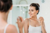 Fotografie beautiful young woman holding perfume bottle and looking at mirror in bathroom