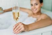 Fotografia vista ravvicinata della bella giovane donna sorridente che tiene il bicchiere di champagne nella vasca da bagno