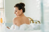 back view of beautiful smiling naked girl sitting in bathtub with foam
