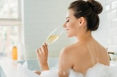 Photo rear view of beautiful smiling girl drinking wine in bathtub with foam