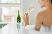 Fotografia ritagliata colpo di sorridente champagne bevente della giovane donna nella vasca da bagno con schiuma