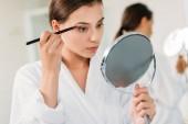 Fotografia bella giovane donna con specchio e applicando ombretto