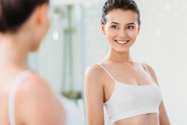selective focus of beautiful smiling girl looking at mirror in bathroom
