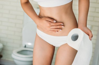 partial view of girl in white underwear holding toilet paper while suffering from diarrhea
