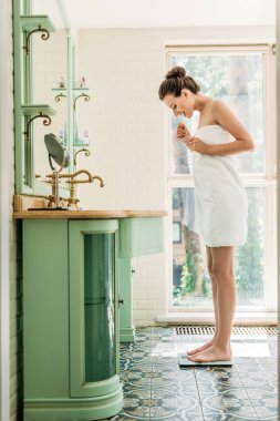 Happy young woman in towel standing on digital scales in bathroom stock vector
