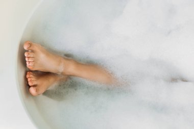 partial view of beautiful female legs in bathtub with foam