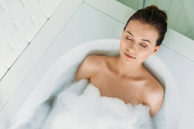 top view of beautiful young woman with closed eyes relaxing in bathtub