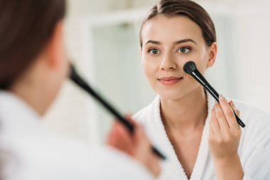 smiling young woman looking at mirror and applying makeup in bathroom
