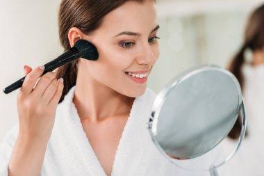 Beautiful smiling brunette girl in bathrobe applying powder bronzer with brush stock vector