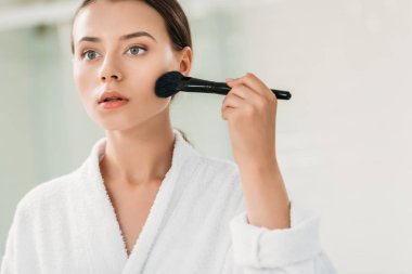 Beautiful girl in bathrobe applying bronzer with brush stock vector