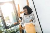 Fényképek mosolygó afro-amerikai üzletasszony állandó modern irodában portréja