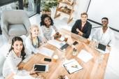 Fotografia vista di alto angolo del gruppo multiculturale di gente di affari che guarda lobbiettivo mentre era seduto al tavolo nella sala conferenze