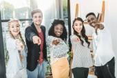 mnohonárodnostní usmívající se lidi ukázal na kameru stoje společně v úřadu