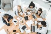 vysoký úhel pohled mladých obchodního týmu diskutovat podnikatelský plán během konference v úřadu