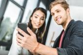szelektív összpontosít, a multikulturális mosolygó munkatárs segítségével okostelefon