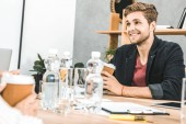 portrait of smiling young businessman sitting at table during meeting in office