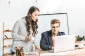 portrét mnohonárodnostní podnikatelé pracují společně na přenosný počítač v kanceláři