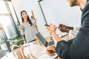 portrait of young asian businesswoman presenting business idea to colleagues during meeting