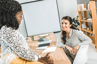 multiethnic smiling businesswomen having conversation at workplace in office