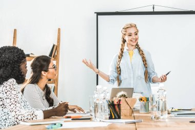 smiling businesswoman presenting new information to multicultural colleagues at business meeting
