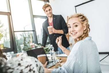 side view of smiling businesswoman with coffee to go sitting at table during business meeting