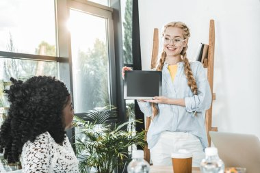 portrait of smiling caucasian businesswoman showing tablet to african american colleague in office