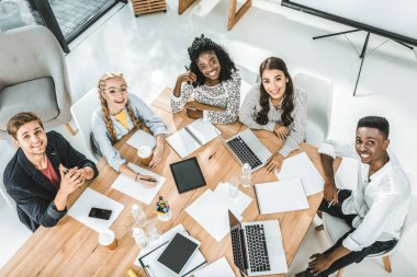 high angle view of young business team looking at camera during business conference in office