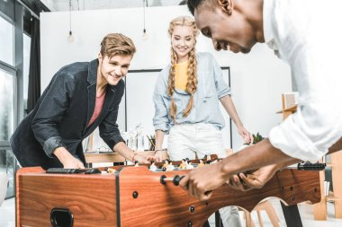businesswoman watching multicultural colleagues playing table football in office