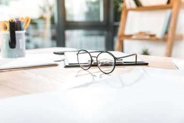 selective focus of round eyeglasses on workplace with papers and clipboard