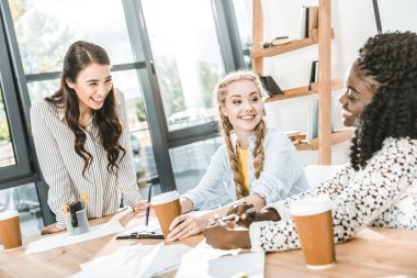 multicultural cheerful businesswomen with coffee to go having conversation in office