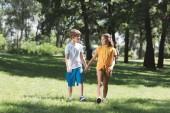 krásné šťastné děti, drželi se za ruce a společně procházky v parku