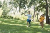 roztomilý šťastné děti hrát s modelem letadla a běží v parku