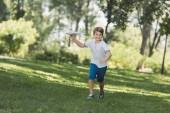 imádnivaló boldog fiú játék síkon gazdaság, és mosolyogva kamera Park