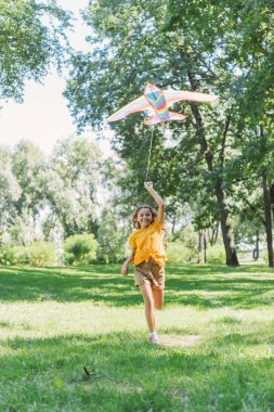 beautiful happy child holding colorful kite and smiling at camera while running on grass in park