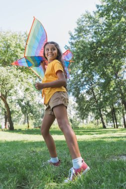 low angle view of cute happy child holding colorful kite and looking away in park