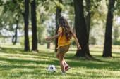 po celé délce pohled roztomilé dítě hraje s fotbalovým míčem na trávě