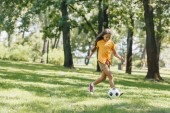 Fotografie beautiful happy child playing with soccer ball in park