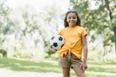 Fényképek szép boldog gyerek tartja a futball-labda, és mosolyogva kamera Park