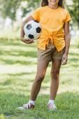 aranyos mosolygós gyermek gazdaság futball-labda, állva a füves Park levágott lövés