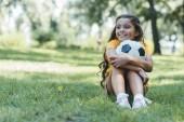 Fényképek imádnivaló boldog gyermek gazdaság futball-labda, és keres el a parkban ülve