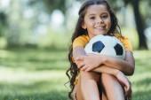 Fényképek imádnivaló boldog gyermek gazdaság futball-labda, és mosolyogva kamera Park