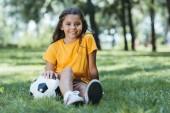 Fényképek aranyos boldog gyermek ül a fűben, a futball-labda, és mosolyogva kamera