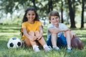 roztomilý šťastné děti s fotbalu a rugby míče sedí a usmívá se na kameru v parku