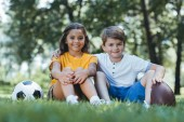 cute happy kids with soccer and rugby balls sitting on grass and smiling at camera
