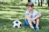Fotografie niedliche kleine Junge auf dem Rasen sitzen und mit Blick auf Fußball