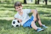 Fotografie adorable happy little boy resting in grass with soccer ball