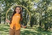 schönes glückliches Kind mit Hula-Hoop-Reifen und lächelnd in die Kamera im Park