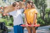 Roztomilý šťastné děti drží skateboardy a usmívá se navzájem v parku